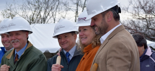 dave adams poses in hardhat at groundbreaking